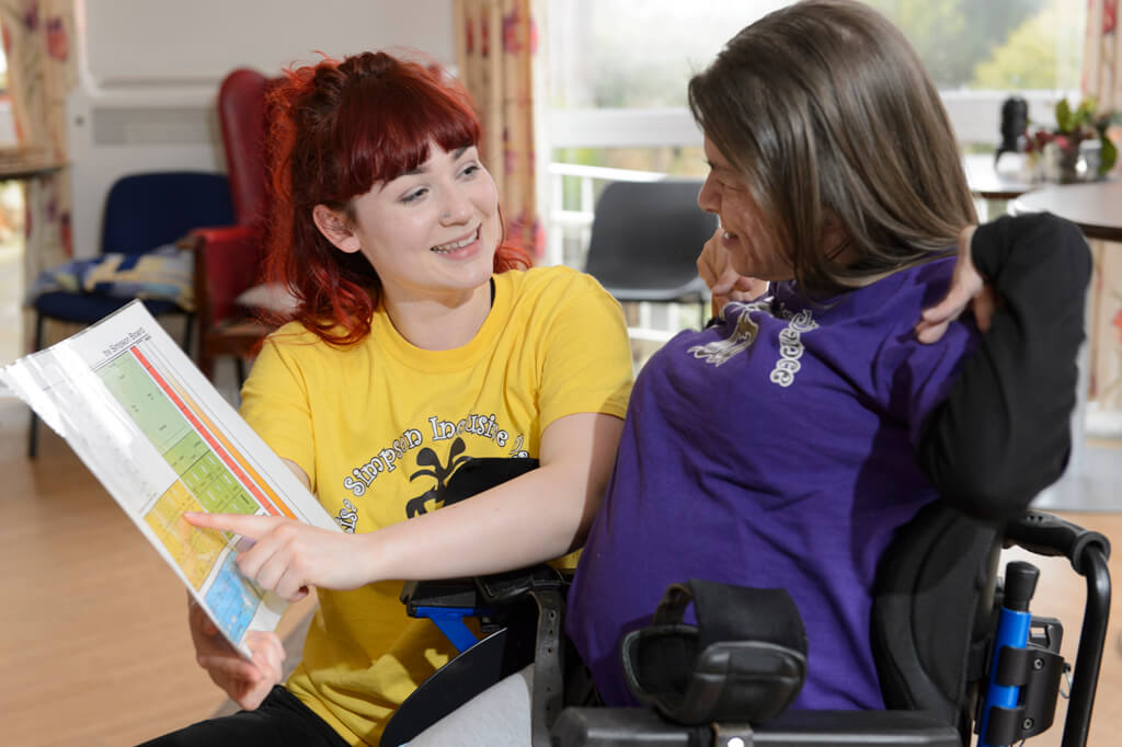 a smiling arts facilitator showing a participant sat in a wheelchair a visual teaching tool as part of a dance workshop
